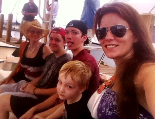 "Alexis, her 3 boys and my mom last summer at South Padre Island-- ""We were on a boat on our way out to go Para-sailing. My first time to do that. Checked it off the bucket list...I'm ALL about the bucket list."""